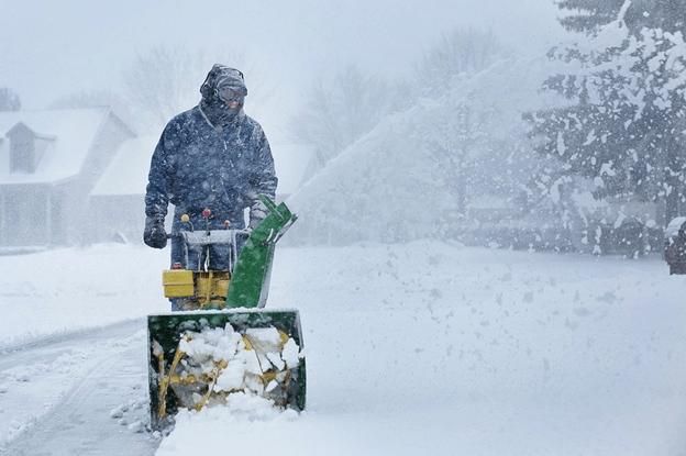Snow Blower- A person operating a snow blower with rotating blades